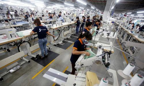 Công nhân làm việc tại một nhà máy dệt may. Ảnh: Reuters